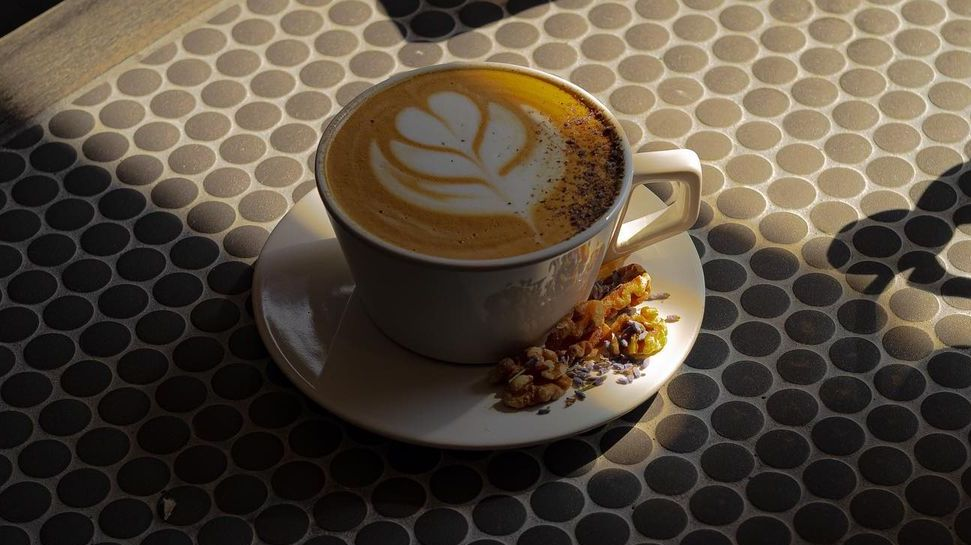 latte served in a mug with toasted walnuts on the side
